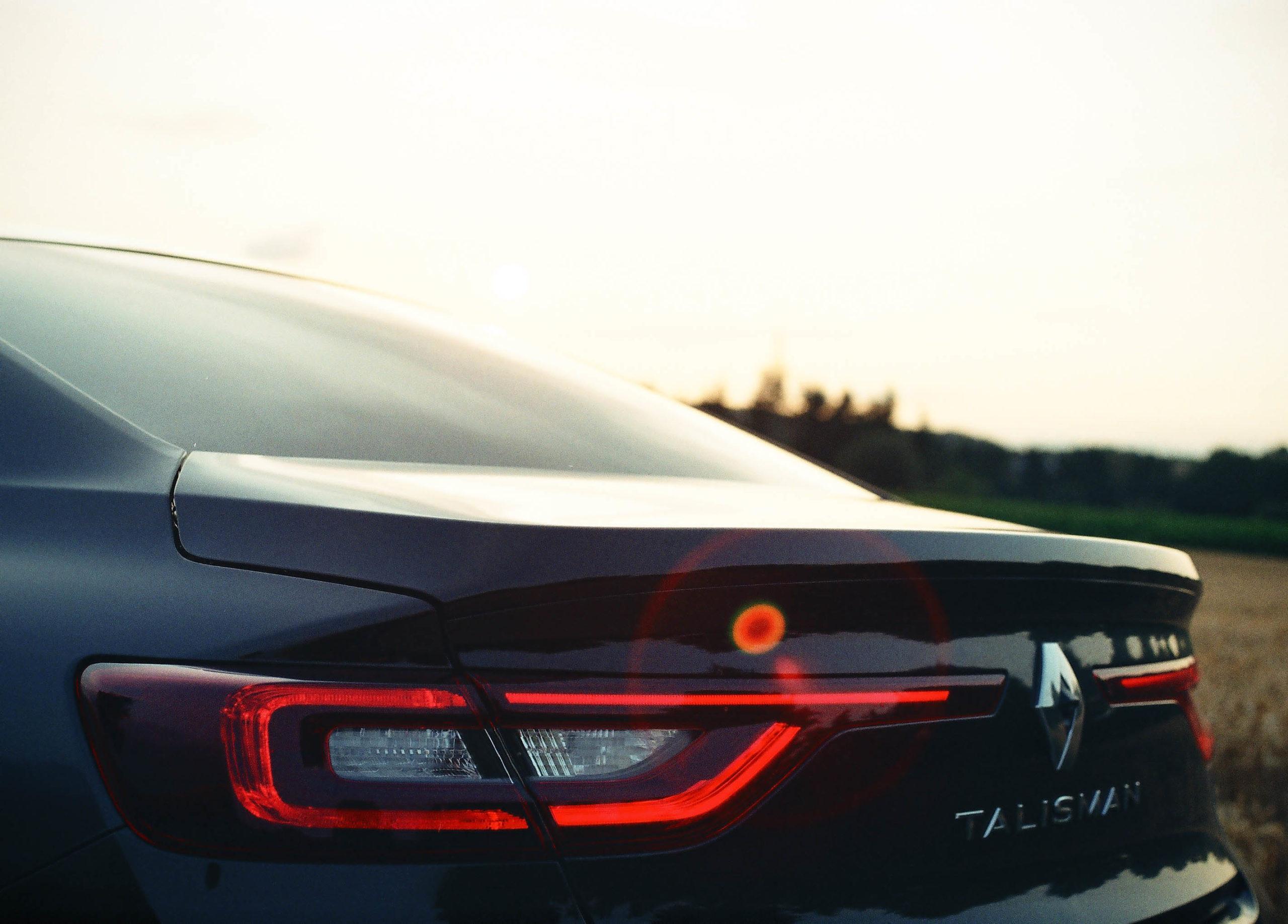 Auto im Sonnenuntergang vor einem Feld