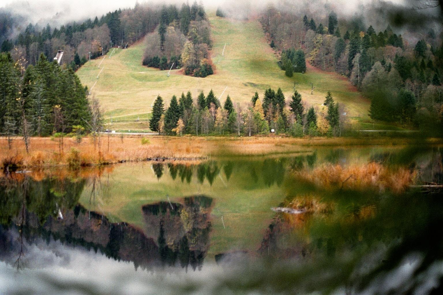 Spiegelnder See mit bergiger Landschaft