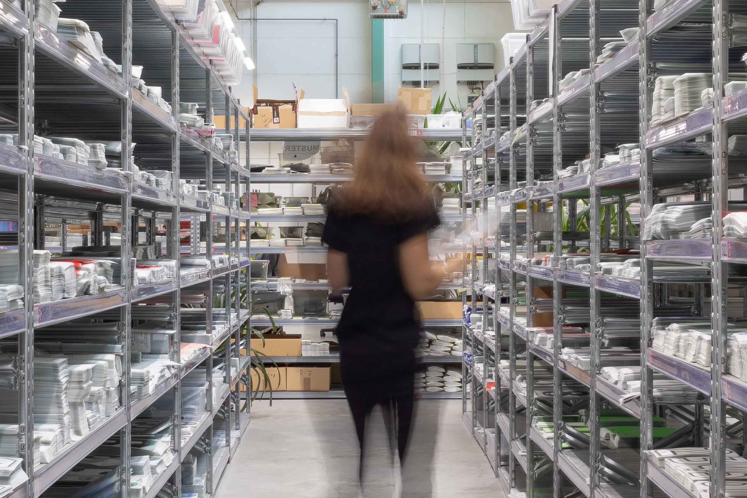 Frau im Gang einer Produktionshalle zwischen Regalen